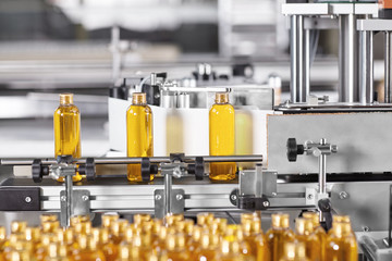 Factory process of production new cosmetics. Glass bottles standing on conveyor line going to be twisted. Automated process on big factory. Production of new shampoo on coveyor belt.Innovation concept