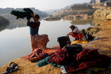 Rohingya refugees wash clothes in a pond at Kutupalang Unregistered Refugee Camp, in Cox's Bazar