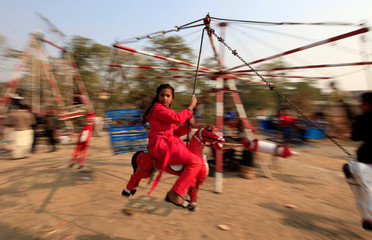 A girl rides on a makeshift merry go round on Christmas Day in Islamabad