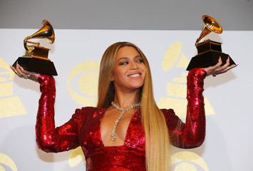 Beyonce holds the awards she won at the 59th Annual Grammy Awards in Los Angeles