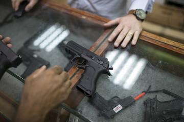 Israeli man looks at guns at a gun shop in Tel Aviv
