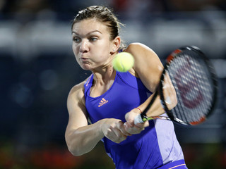 Halep of Romania returns the ball to Makarova of Russia during their women's singles tennis match at the WTA Dubai Tennis Championships
