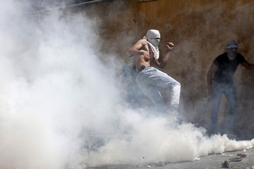A Palestinian protester kicks a gas canister fired by Israeli police during clashes in the East Jerusalem neighbourhood of A-tur
