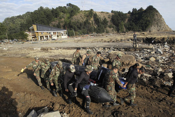 Chilean soldiers carry a rubber dinghy during a search and rescue operation after the earthquake in Constitucion