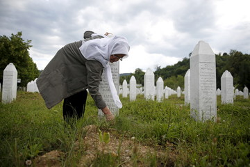 Hajra Catic cleans the grave of her husband in the Memorial center in Potocari