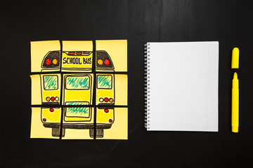 """Back to school background with title """"Back to school"""" and """"school bus"""" written on the yellow pieces of paper and notebook  are on the chalkboard"""