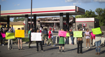 A destroyed QuikTrip store is pictured in the background as demonstrators hold signs while protesting the death of black teenager Michael Brown in Ferguson