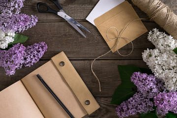 Lilac blossom on rustic wooden background with notebook for greeting message. Top view