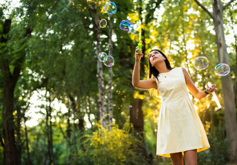 beautiful young woman with yellow dress blowing bubble in the city