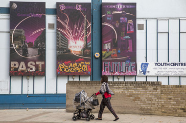 A woman pushes a pram past inspirational murals on a youth centre on the Aylesbury Estate in south London, Britain