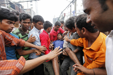 Garment workers assist their colleague during a protest in Dhaka