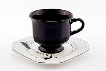 Black retro teacup on white saucer with black rose isolated on white background - English tea