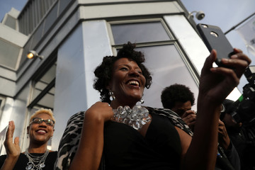 Women smile and take photos during the Valentine's Day wedding ceremony of Roetta Collins and Patrick Smith on top of the Empire State Building in New York