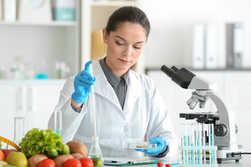 Young female nutritionist testing food samples in laboratory