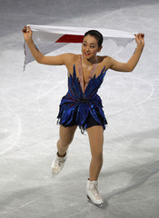 Gold medallist Asada of Japan holds a Japanese national flag during the award ceremony at the ISU World Figure Skating Championships in Saitama