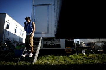 Mexican guest worker Sanchez brushes teeth outside a trailer at the Halifax County Fair in South Boston