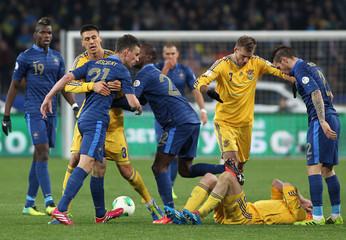 France's Laurent Koscielny (L, front) argues with Ukraine's Olexandr Kucher, who lies on the pitch, during their 2014 World Cup qualifying first leg playoff soccer match at the Olympic stadium in Kiev