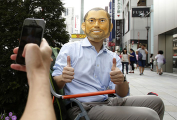 A man wearing a mask depicting the likeness of Apple's co-founder Jobs, poses for pictures as he camps, ahead of the September 19 release of iPhone 6 and iPhone 6 Plus, in front of an Apple Store at Tokyo's Ginza shopping district