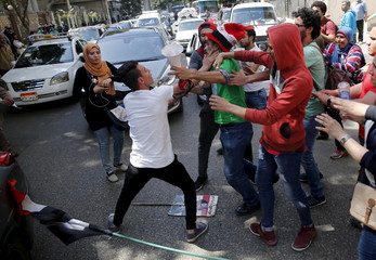 Egyptian protesters clash with a supporter of President Abdel Fattah al-Sisi during a demonstration protesting the government's decision to transfer two Red Sea islands to Saudi Arabia, in front of the Press Syndicate in Cairo