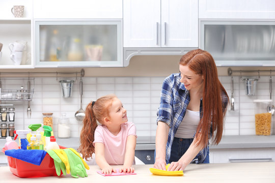 Little girl and her mother cleaning counter in kitchen at home