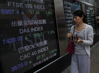 A passerby looks at rising indexes from three major European markets, outside a bank in Hong Kong