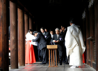 A group of lawmakers including Japan's ruling Liberal Democratic Party lawmaker Hidehisa Otsuji are led by a Shinto priest as they pay their respects to the war dead at the Yasukuni Shrine in Tokyo