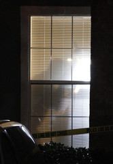 Crime scene photographer is silhouetted against blood splattered window blinds in Grapevine