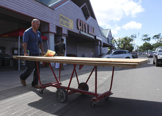 Man leaves the local hardware store with sheets of plywood to board up his windows as a hurricane and a tropical storm approach the Hawaiian islands, in Mililani