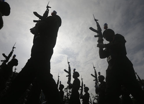 Army soldiers are silhouetted as they march during a rehearsal for Sri Lanka's 67th Independence day celebrations in Colombo