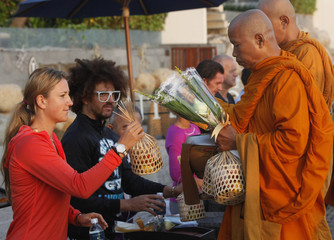 World number one Azarenka of Belarus and rapper Redfoo, a member of hip-hop electro pop duo LMFAO, offers food to Buddhist monks during their visit to Thailand's beach resort city of Hua Hin