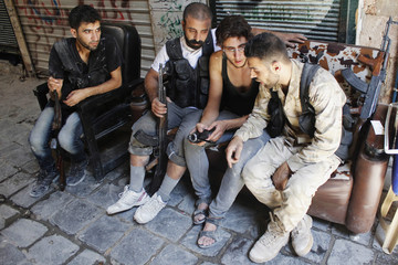 Free Syrian Army fighters watch and react to video footage taken by an activist in old Aleppo