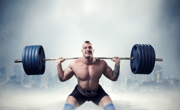 Muscular male weightlifter exercise with barbell
