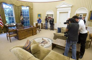 News photographers document the new carpeting, wallpaper and sofas in the Oval Office at the White House in Washington