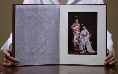 Morimoto shows a photograph of herself and her older twin sister Miho, taken to celebrate their 20th birthdays in 1984, in Otsuki