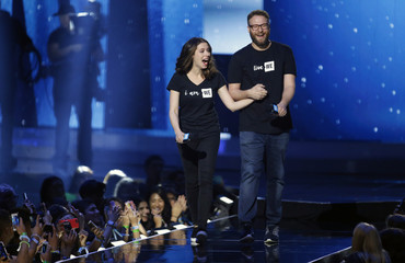 Actors Seth Rogen and Lauren Miller Rogen walk on stage during We Day California in Inglewood