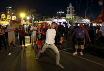 A young man is challenged to  throw baseballs at an arcade at the annual San Diego County Fair