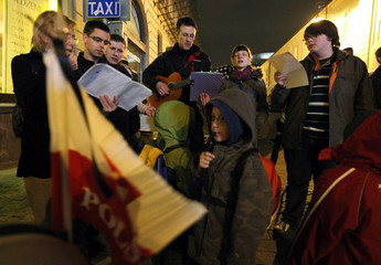 People sing songs as they gather in a square near the Presidential Palace in Warsaw
