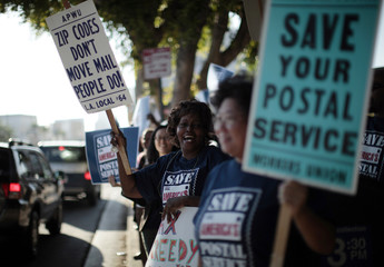 Postal Clerk Elisha Toni joins postal workers in a national day of protest in Los Angeles