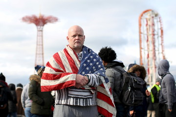 A man wearing a U.S. flag stands on the boardwalk before the Coney Island Polar Bear Club's annual New Year's Day swim at Coney Island in the Brooklyn borough of New York.