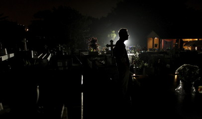 A man stand near graves during a vigil at a cemetery in Barva de Heredia, Costa Rica