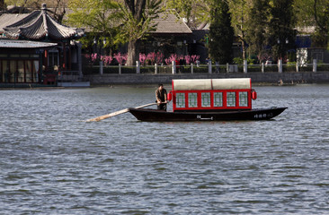 A man rows a boat on Qianhai Lake in Beijing