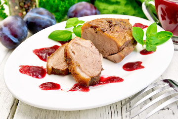 Duck breast with plum sauce in plate on light board