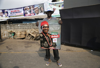 Abubakar Kadakinguda, an ethnic Hausa Muslim man, holds a poster campaigning for Nigeria's former military ruler and presidential candidate for All Progressives Concgress Muhammadu Buhari in Ibadan