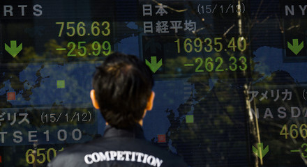 A man looks at an electronic board displaying Japan's Nikkei average in Tokyo