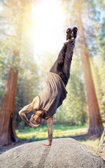 Breakdance performer, upside down motion in forest