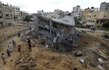 Palestinians gather around the remains of a house which police said was destroyed in an Israeli air strike in Gaza City