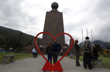 A tourist poses for a picture with a Valentine's Day display at the Middle of the World monument, in Quito,