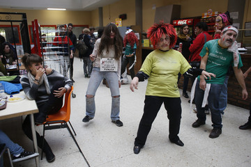 "A student looks at demonstrators dressed as zombies dancing to the music of Michael Jackson's ""Thriller"" song during a protest at the cafeteria of the faculty of Political Science at Madrid's Complutense Universit"