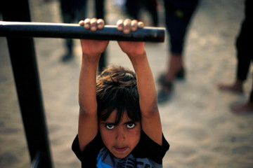 Palestinian boy from Bar Palestine team demonstrates his street workout skills during a training session on a beach in Gaza City