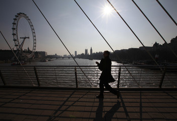A man crosses one of the Golden Jubilee Bridges, near the Houses of parliament and the London Eye, in central London